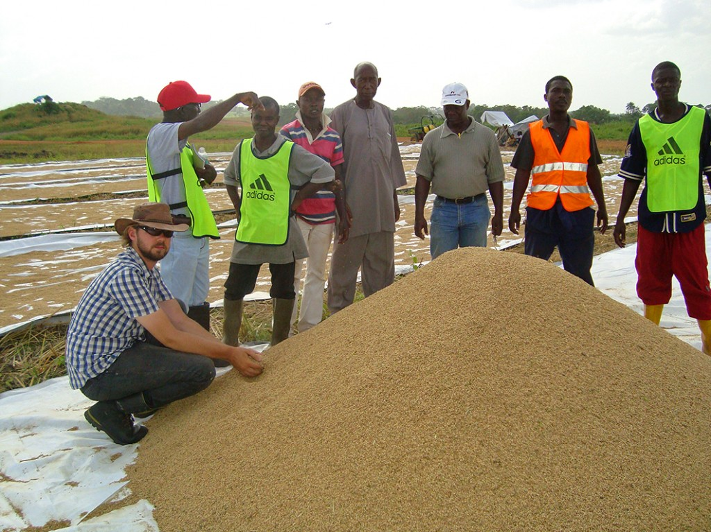 Management team by pile of rice in Liberia